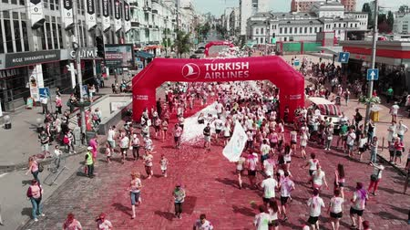 participants : Kyiv  Ukraine - June 2, 2019 - People smeared colorful fluorescent holi paints running at Color Run Kyiv festival. Drone flying around arch Turkish Airlines with participants crossing finish line