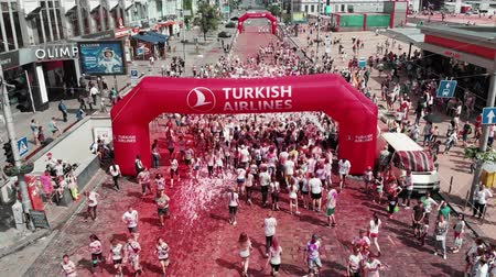participante : Kyiv  Ukraine - June 2, 2019 - Women and men crossing arch Turkish Line at Color Run Kyiv. Finish line with white foam, drone aerial view. Participants smeared in paints at colorful holi festival Vídeos