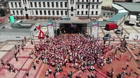 participante : Kyiv  Ukraine - June 2, 2019 - People staying near stage at Color Run Kyiv, aerial drone view. Females and males in the city center at colorful holi festival