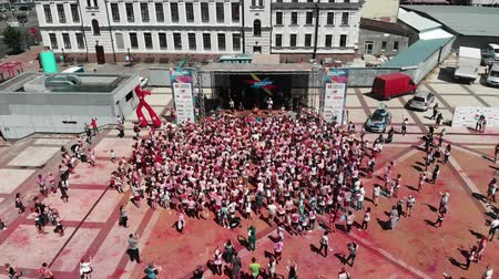 participante : Kyiv  Ukraine - June 2, 2019 - Women and men at holi paint festival. Participants near stage at Color Run Kyiv. Drone flying above center of town with people standing near stage with leading. Vídeos