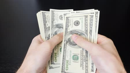 waluta : Man counts his salary. Male hands counting american one hundred dollar bills. Paper money pile in hands. Finance and money payment concept. Man counting money cash