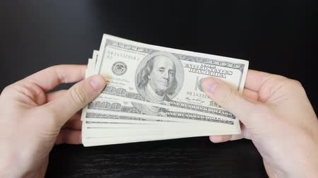 Money cash in male hands. Man holding pile of american one hundred dollar bills. Male hands counting salary. American currency exchange in bank. Finance and money payment concept Стоковые видеозаписи