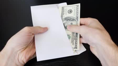 Man puts cash money in envelope. Close up of male hands holding dollar bills and puts money in envelope. Man puts bribe in envelope. Finance and money payment concept