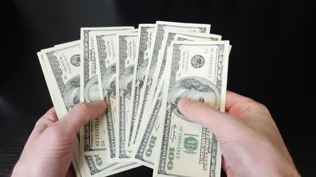 kalkulačka : Hands holding one hundred dollar bills pile. Man counting cash money on office desk. Close up of american dollars. American currency exchange in bank. Finance and money payment concept