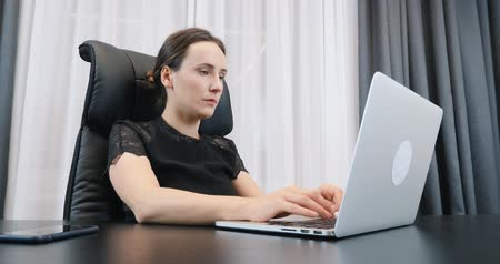 Female working on laptop in the office. Woman typing on computer keyboard. Lady boss in black dress sitting at her office desk Стоковые видеозаписи