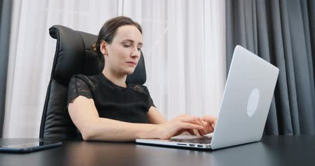 Businesswoman works in office. Caucasian young female typing on laptop keyboard and looking at screen. Woman in black dress sitting at office desk Стоковые видеозаписи