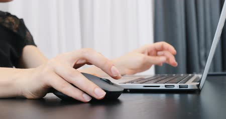 Unrecognized woman hands working on laptop keyboard and mouse. Close up of fingers typing on computer keyboard