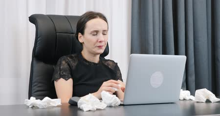 Female with red eyes and runny nose works on laptop in office with dirty napkins lying on table. Woman wipes her nose with paper napkins sitting at her office desk.
