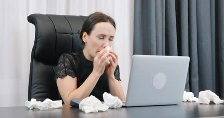 Sick woman with runny nose working in office with dirty paper napkins lying around. Woman blows her nose. Female with illness and red eyes sitting at her office desk and looking at laptop
