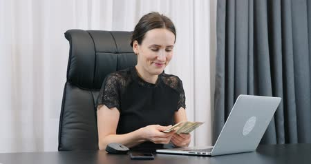 Lady boss counting dollar bills. Woman counts cash money in the office. Young smiling female in black dress with american one hundred dollars bills pile in hands. Success finance business concept Stok Video