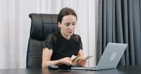 Young confident woman counting american dollar bills in office. Lady boss counts banknotes sitting at office desk. Female holding pile of dollars in hands. Success business concept