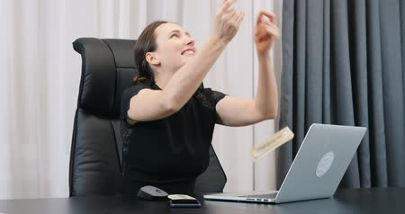 Happy businesswoman with falling money. Lady boss sitting at her modern office desk and dollar bills falling around. Young female happy with falling dollar banknotes
