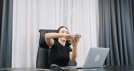 Happy rich woman scattering dollar bills pile. Successful lady boss scatters cash in office. Female throwing money in the air sitting at her office desk Стоковые видеозаписи