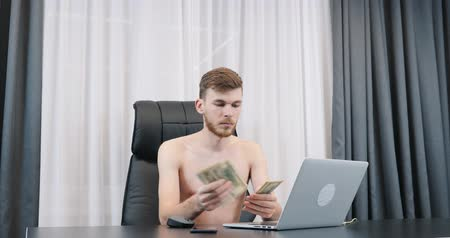fondo industrial : Young man counting dollar bills pile in the office. Male counts money sitting at her office desk. Man holding american one hundred dollar banknotes. Finance and success business concept