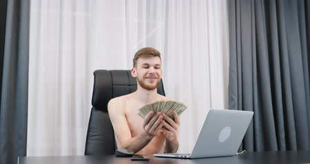Rich successful man counting cash money in modern office. Young happy male counts dollar bills pile. Boy holding cash in hands