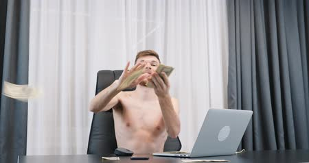 Happy man throwing cash money in the office. Rich successful male scattering american one hundred dollar bills pile in the air. Finance concept