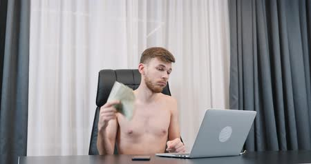 Pathetic man holding american dollar bills pile in hands in the office. Rich successful male holds dollar banknotes and sitting at his office desk. Finance and success business concept Стоковые видеозаписи