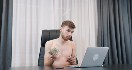 Man counting cash in office. Young successful male counts american one hundred dollar bills. Man holds pile of money in the office. Finance and success business concept Стоковые видеозаписи
