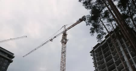 Construction Process of Skyscraper with cranes. High crane works on building site with a house. high rise residential complex under construction. Construction of apartment building in green zone