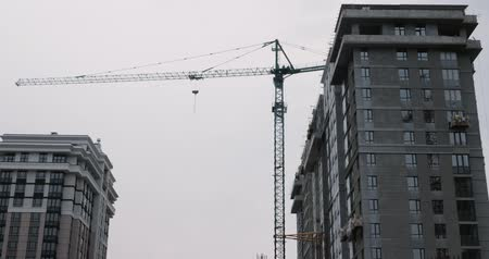 Modern residential complex under construction. Skyscrapers under construction with huge cranes against gray sky and clouds. High crane works on building site with a house