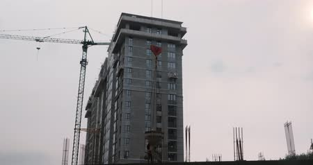 Workers working on the construction site. Builders build a house. Construction site with high crane