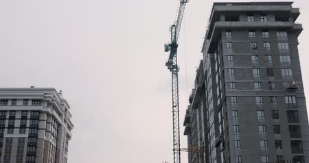 Construction site with crane. High crane works on building. Builders build a house. Crane working on construction site under gray cloudy sky on rainy day