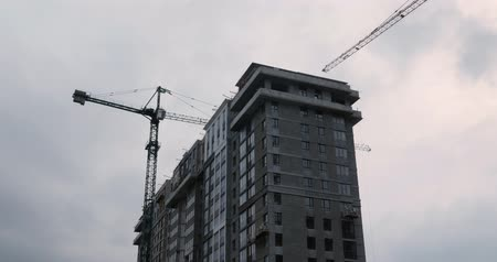 Workers working on the construction site. Construction of apartment building in green zone. Isolated residential complex under construction against gray sky