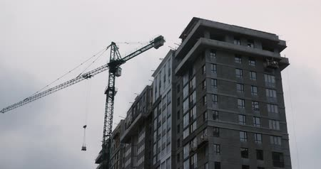 Construction site with high crane. Builders build modern residential complex. Crane working on construction site under gray cloudy sky. Skyscraper under construction with huge crane