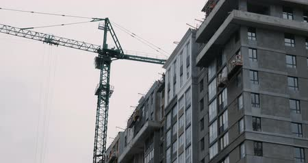 Apartment building under construction with high crane. Builders build house. High crane working on building site Стоковые видеозаписи