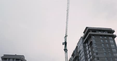 Construction crane works on building site. High rise residential complex under construction. Construction of apartment building in green zone. Skyscrapers under construction with huge crane