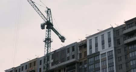 Close up of high construction crane on building site with unbuilt skyscraper. Workers in uniform build a residential modern complex