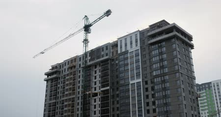 Modern high rise residential complex under construction with huge crane. Construction process. Builders work on building site