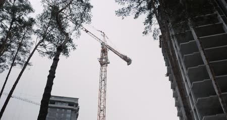 High crane works at construction site at windy day. Building site with high rise residential modern complex in green area surrounded by forest Стоковые видеозаписи