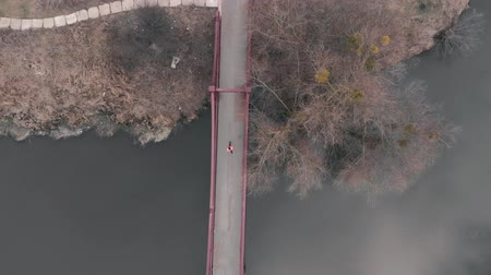 Aerial top view of woman running across bridge. Sportive female athlete in bright jacket runs on bridge across river in city park. Motivated young girl running outdoor