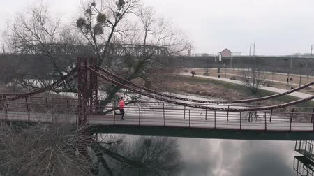 Caucasian female athlete is running across river in city park. Woman doing outdoor morning exercises in park. Aerial drone view of girl in orange jacket runs on bridge across river