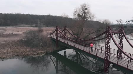 Woman is running on bridge across river, aerial drone view. Brunette female athlete runs in park with river and promenade. Girl practicing running exercises in recreation area Стоковые видеозаписи