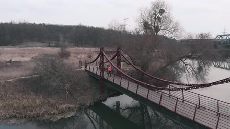Young girl is jogging on bridge across river. Sportive woman athlete runs in park with river and bridge, aerial drone view. Female running near parkland with river