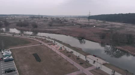 water rail : Pedestrian recreation area with river and car parking from birds eye view. Aerial drone view of parkland with people walking along promenade