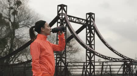 refresh : Caucasian brunette woman drinks energy drink from bottle outdoor. Female athlete in orange bright jacket drinking water from bottle in park. Sport and running concept Stock Footage