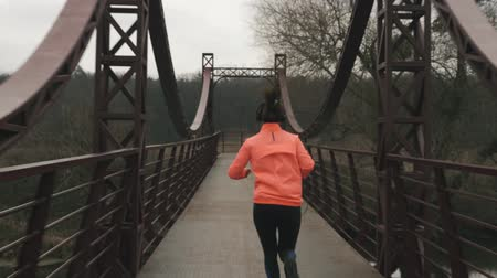 rajstopy : Woman in headphones is running across bridge in park. Young sportswoman in orange jacket and black tights runs on bridge across river outdoor. Sports and healthy lifestyle concept