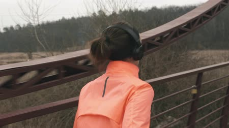 back side : Back side view of brunette woman in headphones running across bridge. Sportive female athlete training outdoor. Young athlete runs on bridge Stock Footage