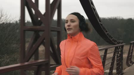 keresztül : Portrait of young woman in headphones runs across bridge. Brunette female athlete in orange jacket jogging outdoor in park. Sportswoman training in parkland