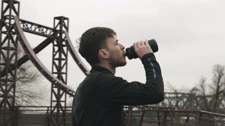občerstvení : Young man drinking water from bottle. Sportive male athlete drinks energy drink during training. Sports and running concept Dostupné videozáznamy