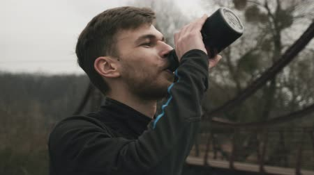 občerstvení : Portrait of male athlete drinking water from bottle. Caucasian young man in black sports clothes drinking energy drink from bottle in park. Close up of attractive sportsman face in park