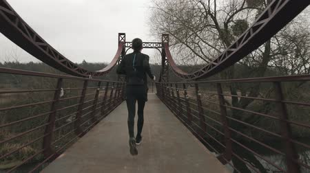 Sportive thin man runs on bridge across river in park, backside view. Male athlete running outdoor. Young guy in black tights and jacket jogging and doing morning exercises
