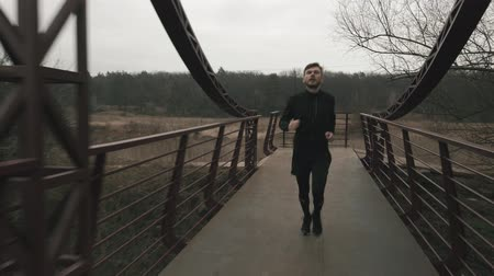 Male runs on bridge across river, front view. Caucasian young man in sports clothes running outdoor in park at gray cloudy day. Thin guy training in forest with river and bridge
