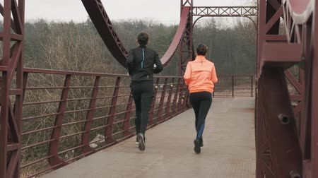 Athletes run on bridge across river. Young caucasian couple jogging in park, backside view. Male and female are running outdoor in the morning