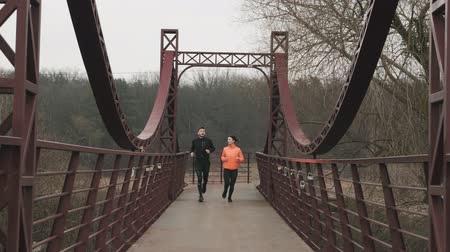 Motivated young couple training in park. Sportive young woman and man are jogging across pedestrian bridge. Female and male athletes running together. Sports and run concept Стоковые видеозаписи