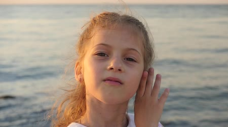brincos : adorable little girl on a background of sea sunset shows and inflate her lips Stock Footage