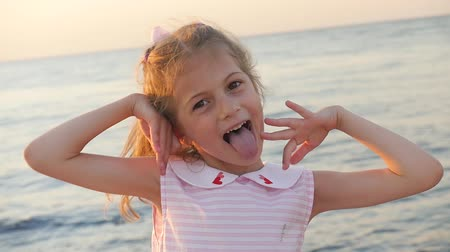 гримаса : beautiful small girl grimaces and shows tongue on the background of the sunset sea Стоковые видеозаписи